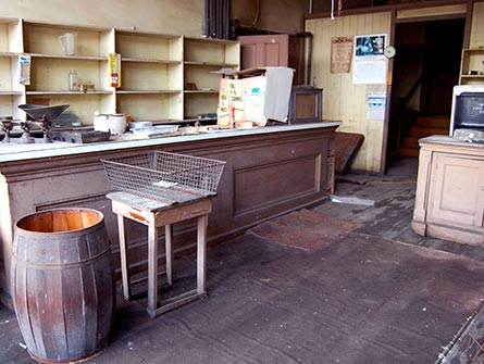 The retail shop counter with aged bread pans, a metal scale, cookware, and an old Camel cigarette advertisement.