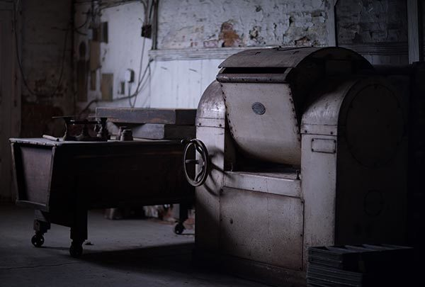 A wooden kneading trough and a rusted electric dough kneader are pushed against the southeast wall of the oven room at the Reher bakery. The white paint on the walls is peeling.