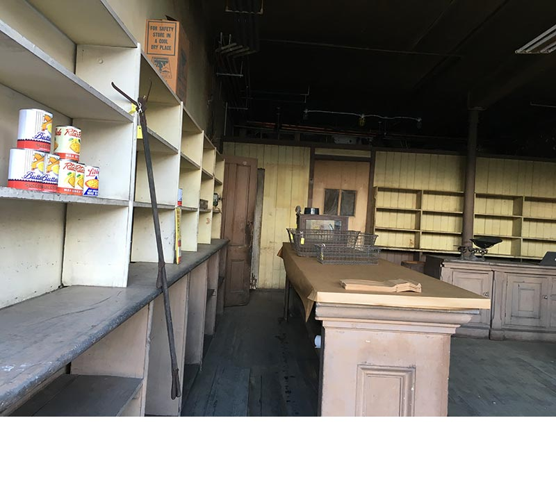The southern half of the retail shop features replica canned goods on the shelves and a metal grabber to retrieve the cans, as well as wire baskets and paper bags on the counters.