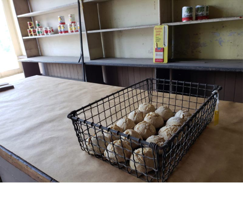 "A wire basket full of 15 ""smooth"" rolls sits on the counter in the retail shop."