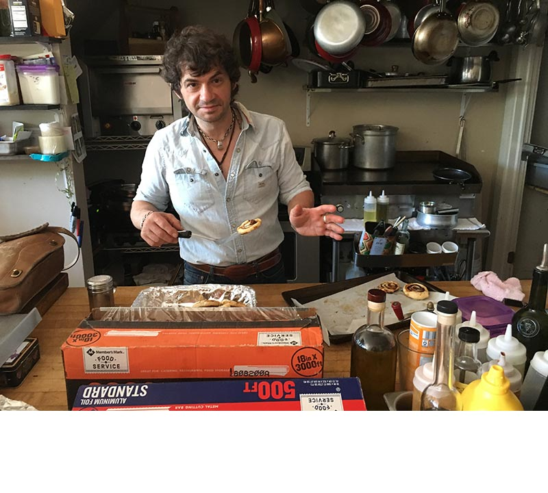 Graziano Tecchio, owner of Graziano's Downtown Cafe, poses with a batch of rugelach in his kitchen.