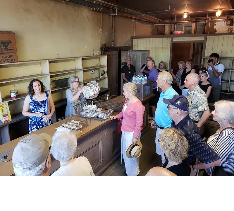 Director Sarah Litvin gives a tour to about 18 people in the historic retail shop.