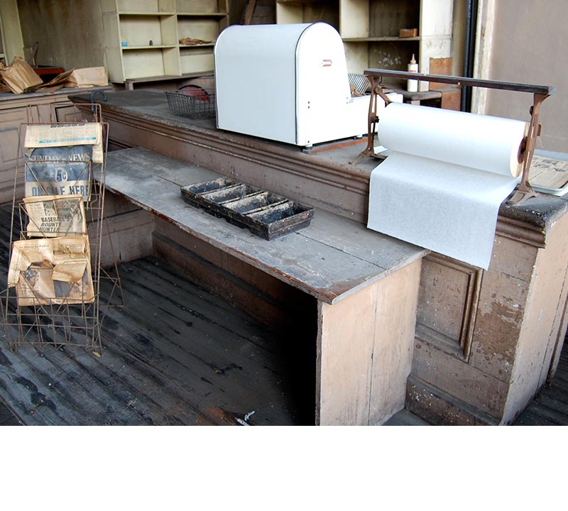 The white, old fashioned bread slicer sits on the counter with other items related to the bakery. A newspaper rack with yellowed papers stands in front of the counter.
