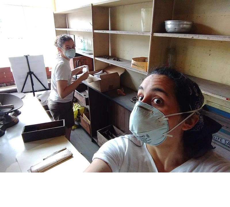 Sarah Litvin and Samantha Gomez-Ferrer wear dust masks while inventorying, cataloging, and preserving the artifacts in the retail shop in 2017..