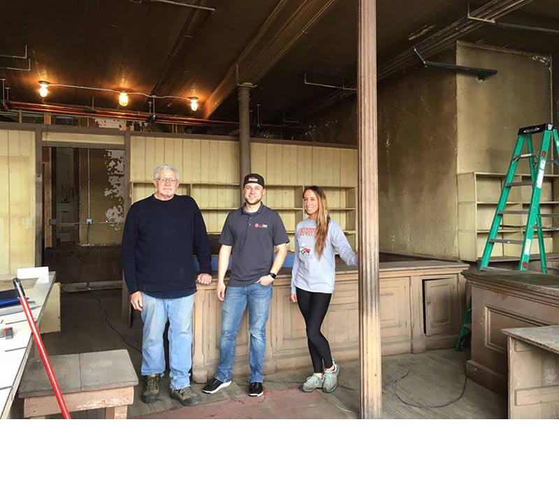 Board chair Geoff Miller and two professional cleaners pose for a photo in the empty and cleaned historic retail space of the bakery in 2018