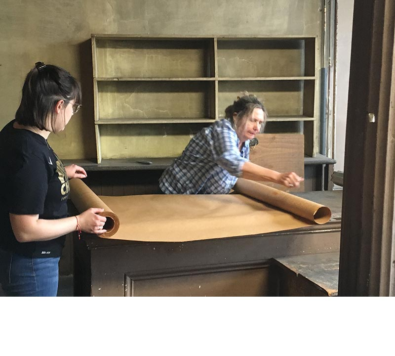 Two people cover the counter in the bakery in butcher paper after the 1980s Formica countertop was removed.