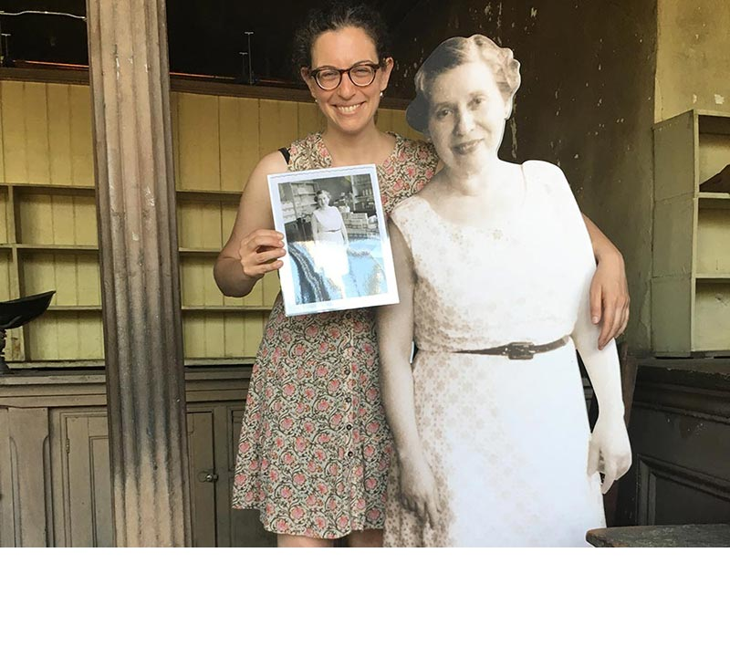 Sarah Litvin poses with a life-size, black-and-white cut out of Sadie Reher while holding the photo on which the cut out was based.