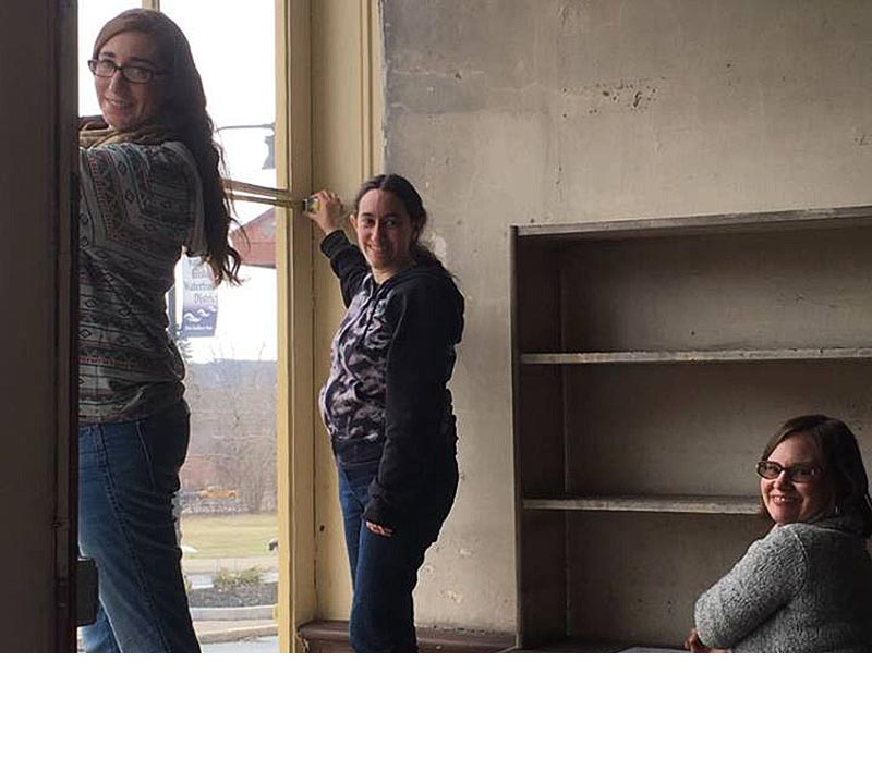 Two students and their professor measure the storefront windows in the historic retail shop of the Reher bakery.
