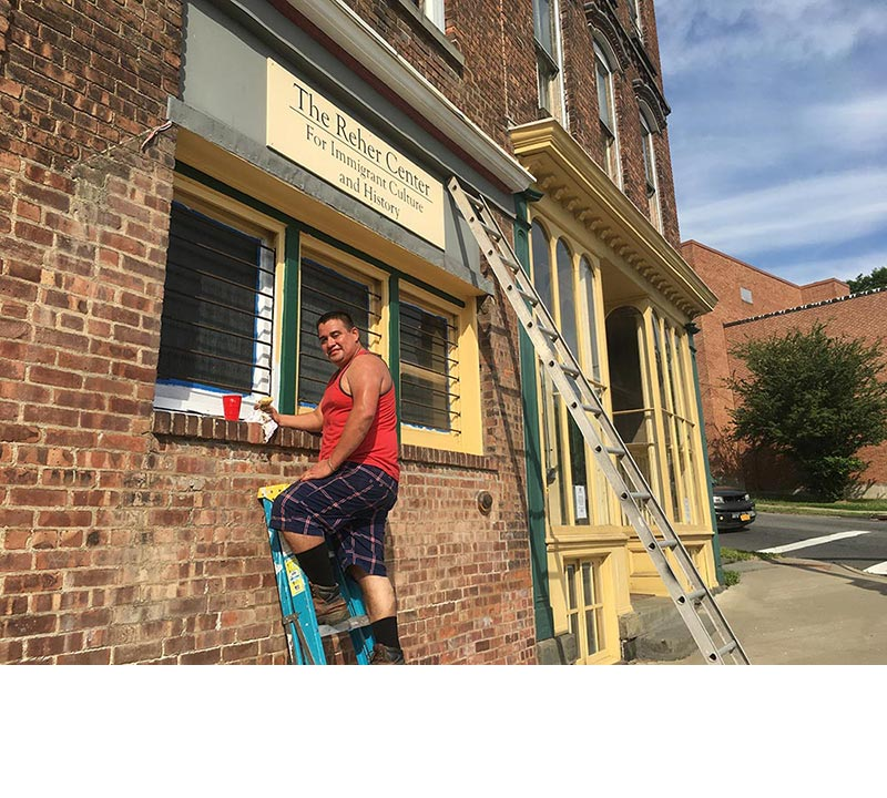 A man paints the exterior of the windows of the oven room the Reher bakery yellow and green, restoring them to their original colors.