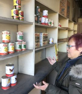 BC Gee looks at the half-filled shelf of Reher's Bakery. Canned foods with colorful labels and boxes of cornflakes are on the shelves.